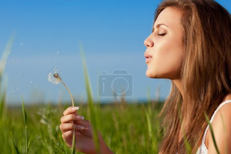 Woman blowing to dandelion