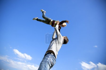 Photo for Father turns to his son's hands on blue sky background - Royalty Free Image