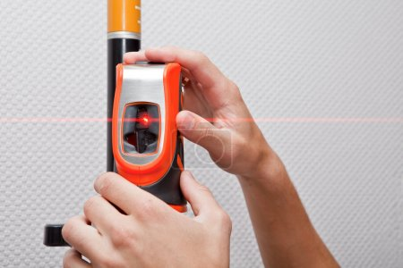 Photo for Man hands measuring with laser level gage - Royalty Free Image