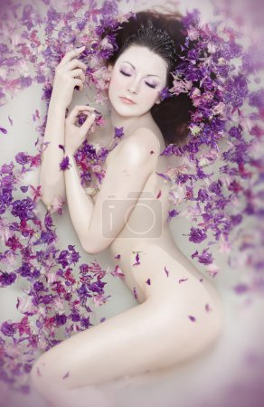 Attractive naked girl enjoys a bath with milk and rose petals. Spa treatmen
