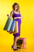 Pregnant woman looking inside shopping bags