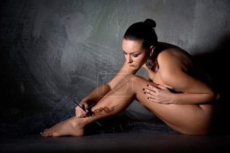 Beautiful young woman applying a temporary tattoo on her leg