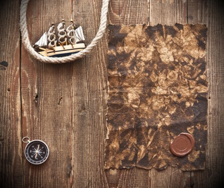 Old paper, rope and model classic boat on wood bac...