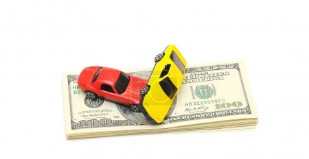 Photo for Toy car accident over a lot of dollar bills isolated on white - Royalty Free Image