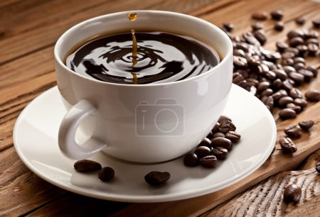 Photo for Drop falling into a cup of coffee. On a wooden background - Royalty Free Image