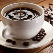 Drop falling into a cup of coffee. On a wooden bac...