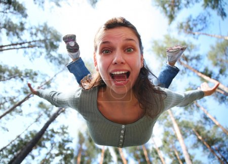 Woman falls from above the pine forest directly at...