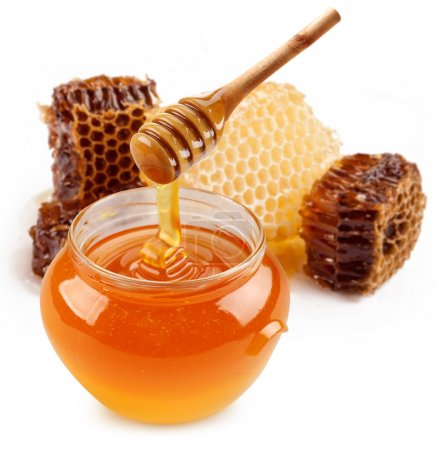 Pot of honey and wooden stick are on a table....