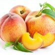 Ripe peach fruit with leaves and slises on white b...