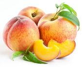 Zralé plody broskví s listy a slises