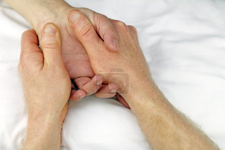 Photo for Male massage therapist hands massaging the hand of another man near the wrist. - Royalty Free Image