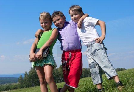 Photo pour Trois enfants heureux au pré avec des livres - image libre de droit