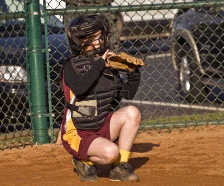 Photo for A young girl behind home plate watching intently ready to make a play. - Royalty Free Image