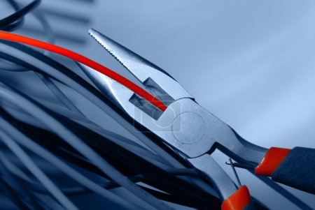 Photo for Pliers cut the red cable closeup on blue background - Royalty Free Image