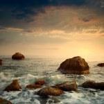Sunrise on rocky sea coast and blurred water...