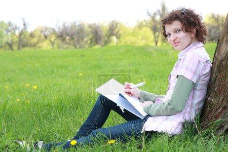 Photo pour Étudiante dans le parc écrit dans un livre d'écriture - image libre de droit