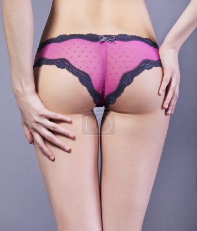 Women's Booty in pink lace panties on a gray background