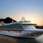 Luxury cruise ship sailing from port on sunrise....