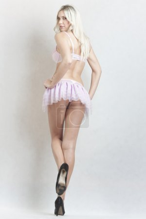 Photo for Beautiful blond girl in sexy pink mini skirt - Royalty Free Image