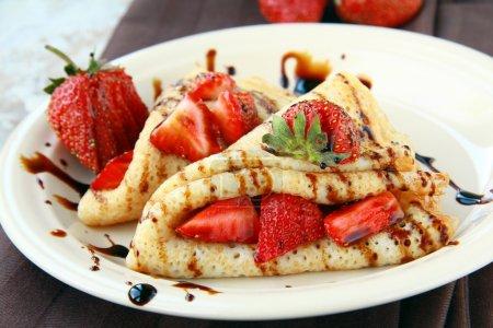 Photo pour Crêpes sucrées à la française, servies avec fraises, sauce au chocolat - image libre de droit