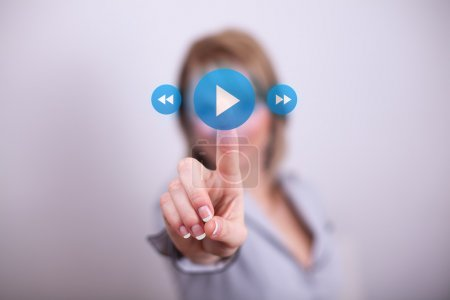 Woman pressing play media button