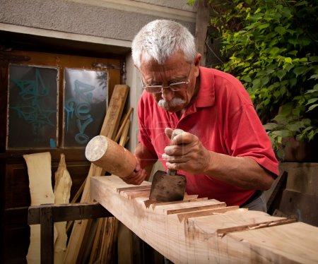 Photo pour Vieux sculpteur sur bois travaillant avec maillet et ciseau 5 - image libre de droit