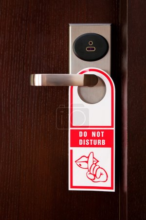 "Hotel door handle with ""do not disturb"" sign"