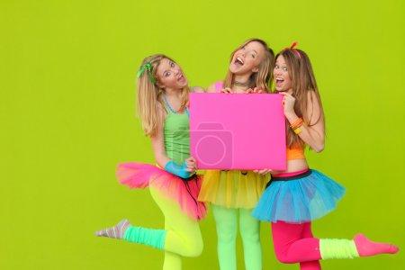 Happy party or fancy dress girls with blank board