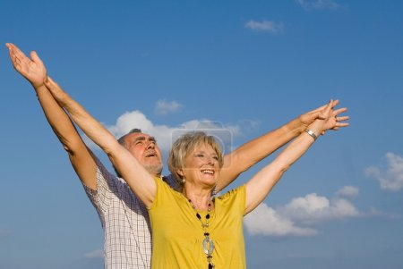 Healthy active christian senior couple arms raised in praise