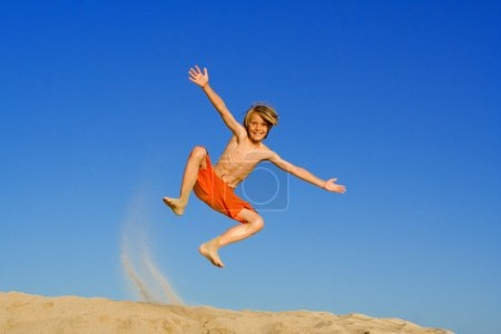 Child jumping and playing on beach summer vacation or holiday