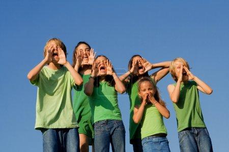 Happy group of school kids shouting, cheering or singing