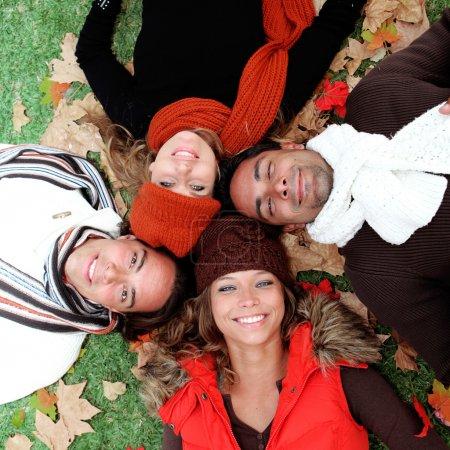 Groupe des heureux souriant de jeune adultes en automne