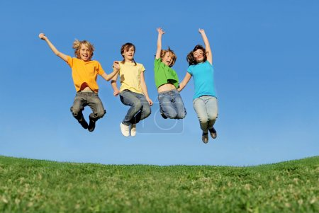 Fit healthy children jumping outdoors in summer