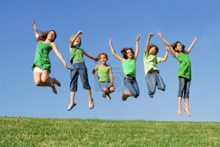 Photo for Happy group of mixed race kids at summer camp or school jumping - Royalty Free Image