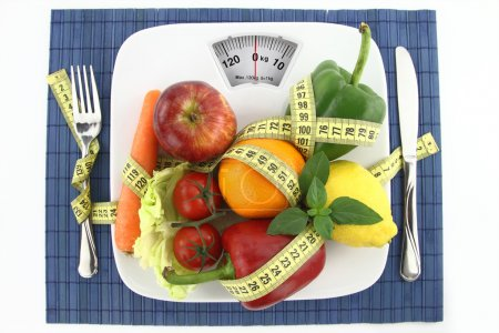 Photo for Fruits and vegetables with measuring tape on a plate as weight scale - Royalty Free Image