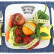 Fruits and vegetables with measuring tape on a pla...