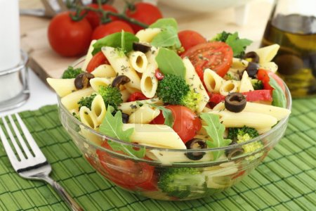 Penne pasta salad with vegetables and herbs