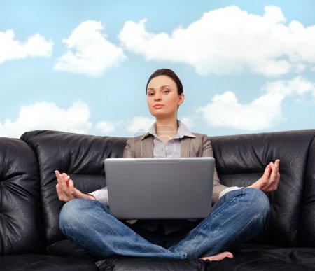 Portrait of young business woman sitting with a laptop on comfor
