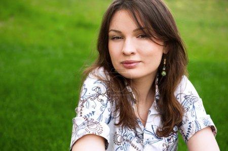 Photo pour Portrait rapproché de jolie jeune femme reposant sur l'herbe et souriant - image libre de droit