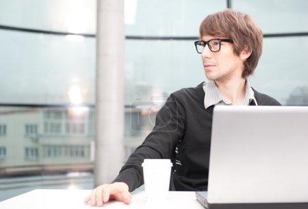 Photo pour Amicale exécutif assis devant l'ordinateur portable dans son bureau. grande fenêtre à l'arrière-plan. à la recherche, rêverie - image libre de droit
