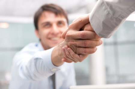Photo for Closeup of business shaking hands over a deal at office - Indoors - Royalty Free Image