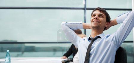 Retrato de un hombre de negocios joven y guapo apoyado en el wi