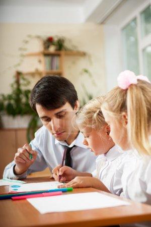 Teacher helping students with schoolwork in school classroom. Ve