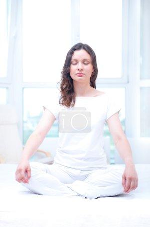Photo pour Jeune femme méditant les yeux fermés dans une chambre lumineuse assise sur le lit - image libre de droit