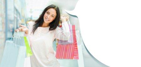 Photo pour Photo de jeune femme joyeuse avec des sacs à provisions sur le fond des vitrines de magasins au centre commercial. elle est souriante et la marche. vide ballon blanc avec fond pour vous - image libre de droit