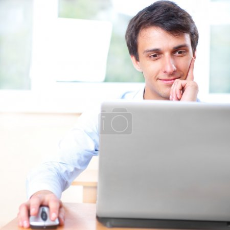 A young man sitting in front of a laptop in his office