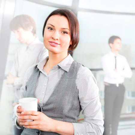 Portrait of a cute business woman with colleagues at the backgro