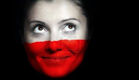 Photo pour Sa fin vers le haut d'un drapeau polonais sur un visage femal sur fond noir - image libre de droit