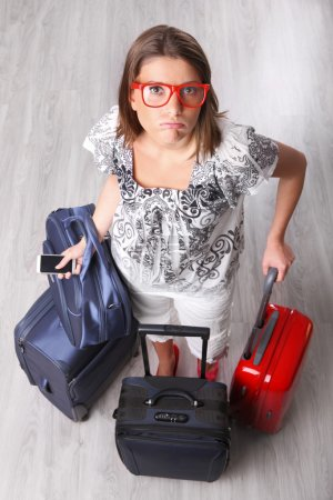 Photo for A picture of a young woman waiting with many pieces of luggage at the airport - Royalty Free Image