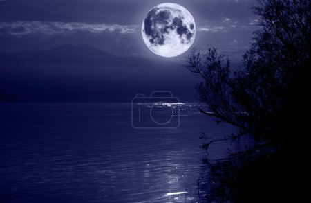 Photo for Big blue moon over water - Royalty Free Image